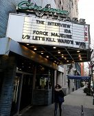NEW YORK CITY - TUESDAY, DEC. 30, 2014: A woman walks under a movie theater marquee showing Sony Pictures film The Interview. The film prompted a North Korean government  computer hack of Sony