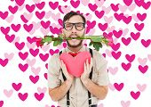 Geeky hipster offering valentines gifts against valentines day pattern