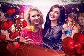 Friends drinking cocktails against valentines heart design