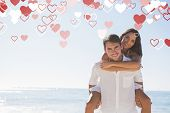 Smiling man giving girlfriend a piggy back looking at camera against valentines heart design