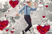 Geeky hipster dancing to vinyl against grey valentines heart pattern