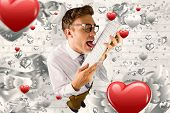 Geeky businessman licking his keyboard against grey valentines heart pattern