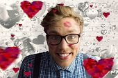 Geeky hipster covered in kisses against grey valentines heart pattern