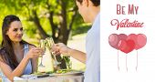 Couple toasting champagne flutes at an outdoor caf�?�© against cute valentines message