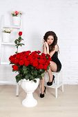 stock photo of legs apart  - Sexy brunette woman with bouquet of red roses against th wall in modern interior apartment - JPG