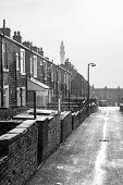 foto of victorian houses  - A rainy wet day in Yorkshire showing a typical Victorian terraced street leading towards a folly named Victorian Wainhouse Tower silhoutted by a misty sky - JPG