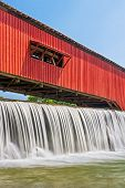 image of covered bridge  - Water falls over the mill dam at the historic red covered bridge in the Parke County Indiana town of Bridgeton - JPG