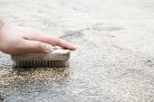Cleaning An Outdoor Floor In A House Area By Brushing With A Brush