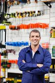 Portrait of confident worker standing arms crossed in hardware shop