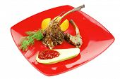 main entree : grilled beef small ribs served with mango fruit and filled avocado on red dish isolated over white background
