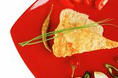 food : vegetable casserole triangle on red plate with cheese and tomatoes isolated on white with hot pepper and chives