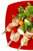 fresh chicken kebabs on red served with cherry