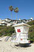 An unmanned lifeguard tower on a beach where the wealthy reside.
