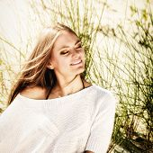 foto of dune grass  - Portrait of beautiful young woman breathing fresh air with closed eyes while sitting on beach sand dunes with grass and enjoying the sun on vacation - JPG