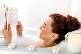 foto of bathing  - Young woman reading book while lying in the bath with foam and candles - JPG