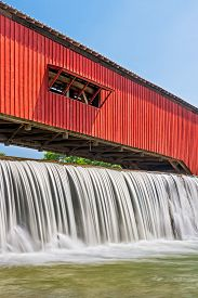 picture of yesteryear  - Water falls over the mill dam at the historic red covered bridge in the Parke County Indiana town of Bridgeton - JPG