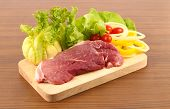 picture of pork chop  - raw pork meat with vegetable on chopping block - JPG