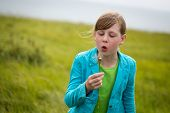 image of dandelion seed  - Outdoor summer portrait of a young blond girl blowing the seeds of a dandelion into the wind - JPG