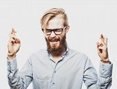 foto of fingers crossed  -  Portrait of young bearded man wearing glasses in shirt keeping fingers crossed and eyes closed while standing against white background - JPG