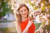 image of nose  - Young woman in red dress standing among blossom trees during sunny day and wiping her nose - JPG
