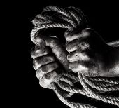foto of gallows  - Male hand with rope on black background - JPG
