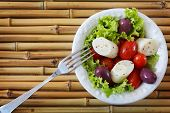 picture of black-cherry  - Fresh salad of heart of palm (palmito) cherry tomatos olives black pepper on white plate with fork on bamboo. Selective focus. Copy space ** Note: Shallow depth of field - JPG
