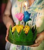 image of traditional attire  - Woman holding boat with candles and flowers are given for Thailands traditional Loy Krathong Festival - JPG