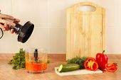 foto of blender  - Hands of chef are going to shred vegetables in a blender - JPG