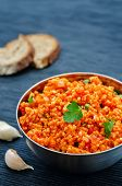 image of millet  - millet porridge with tomato sauce garlic and parsley on a black background - JPG