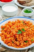 foto of millet  - millet porridge with tomato sauce garlic and parsley on a white wood background - JPG