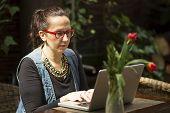 foto of internet-cafe  - Female freelancer with a laptop in a summer cafe - JPG