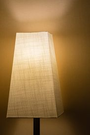 foto of lamp shade  - A lamp with a cloth lamp shade in a dark room against a simple wall - JPG