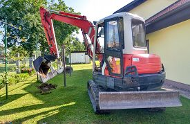 stock photo of excavator  - Rebuilding a house and digging dirt with excavator - JPG