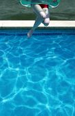 Young Woman Jumping In Swimming Pool