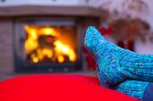 Постер, плакат: Feet in woollen blue socks by the fireplace
