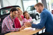 Happy family in car dealership choosing their new car, friendly car agent helping  poster