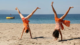 foto of beach party  - two girls in orange clothes doing cartwheel on the beach - JPG