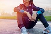 Young athlete sitting on ground to relax after jogging at sunset. Athletic fitness woman sitting on  poster