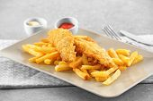 Plate with tasty fried fish and chips on table poster