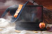 The Concept Of Halloween: A Laptop, A Witch Hat And A Broom, Free Space For Your Advertising. poster