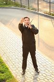Male security guard with portable radio, outdoors poster