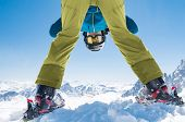 Sporty man bending down playing in snow with ski. Man having fun while skiing on snowy mountain. Hap poster