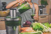 Woman juicing making green juice with juice machine in home kitchen. Healthy detox vegan diet with v poster
