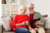 christmas, holidays and people concept - happy senior couple with tablet pc computer at home poster