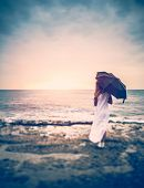 Sadness concept, rear view of a woman with umbrella on the beach, girl in overcast weather looking o poster