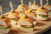 Mini burgers for baby shower party on wooden plate, closeup poster