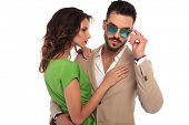 sexy man fixing sunglasses while embracing his woman; young elegant couple standing embraced on whit poster
