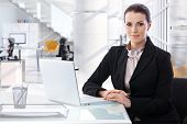 Attractive mid adult brunette caucasian businesswoman sitting at table with laptop computer at brigh poster