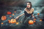 Halloween Witch with Pumpkins and magic lights in a dark room. Beautiful young sexy woman in witches poster
