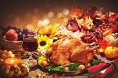 Roasted whole turkey on festive rustic table with autumn decoration for Thanksgiving Day poster